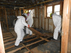 Iowa AmeriCorps Disaster Response Team members removing the flooring in a home impacted by Hurricane Sandy in Long Island.