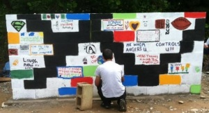 A student painting on the art wall